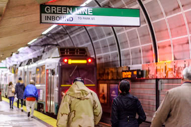People walking towards Green Line train inside North Station