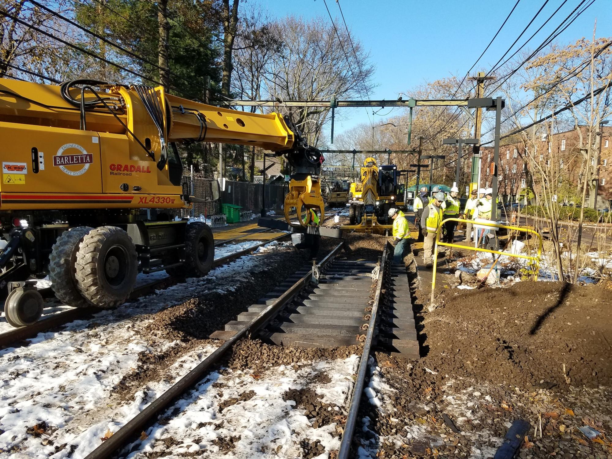 Placing ties. Machinery on the left, a construction crew on the right.