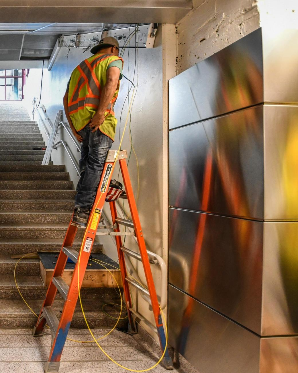 A crewman on a ladder near stairs in Wollaston Station, in the final stages of renovation. (August 7, 2019)