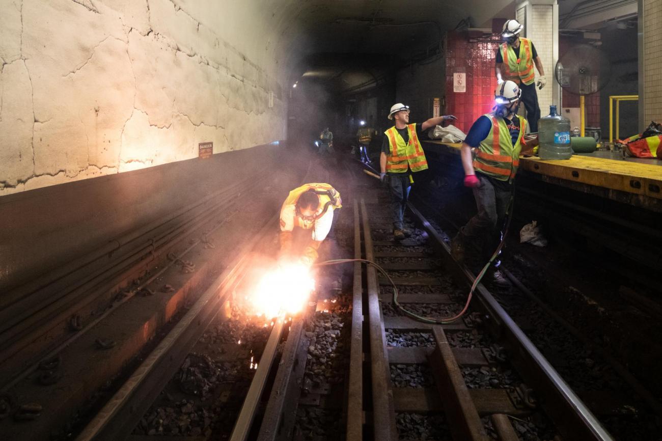 A crew member uses a torch to cut rail near Bowdoin Station.
