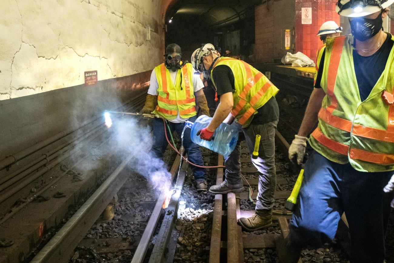 A crew member cools down rail after track welding near Bowdoin Station.