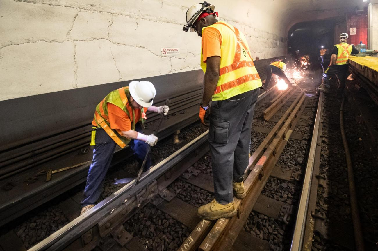 A crew member separates joints of rail, as other workers weld rail in the background, during track replacement work near Bowdoin.