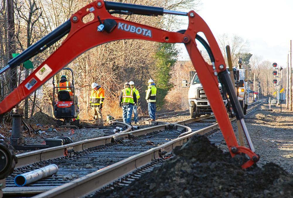A crew excavates underneath the track to prepare for communication signal line installation near Walpole Station on the Franklin Line of the Commuter Rail (January 2020)