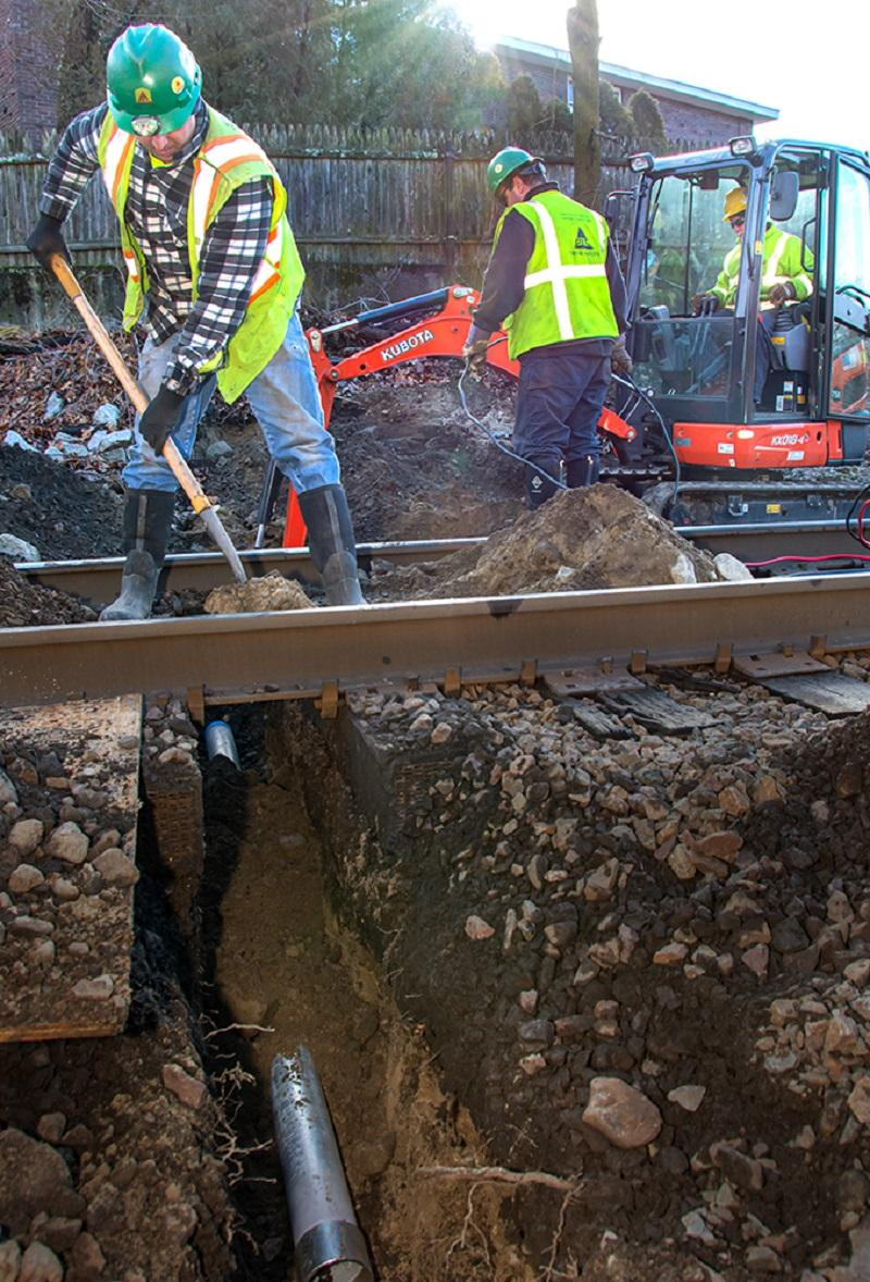 A crew excavates underneath the track where signal communication line will be installed as part of the PTC upgrades on the Franklin Line of the Commuter Rail (January 2020)
