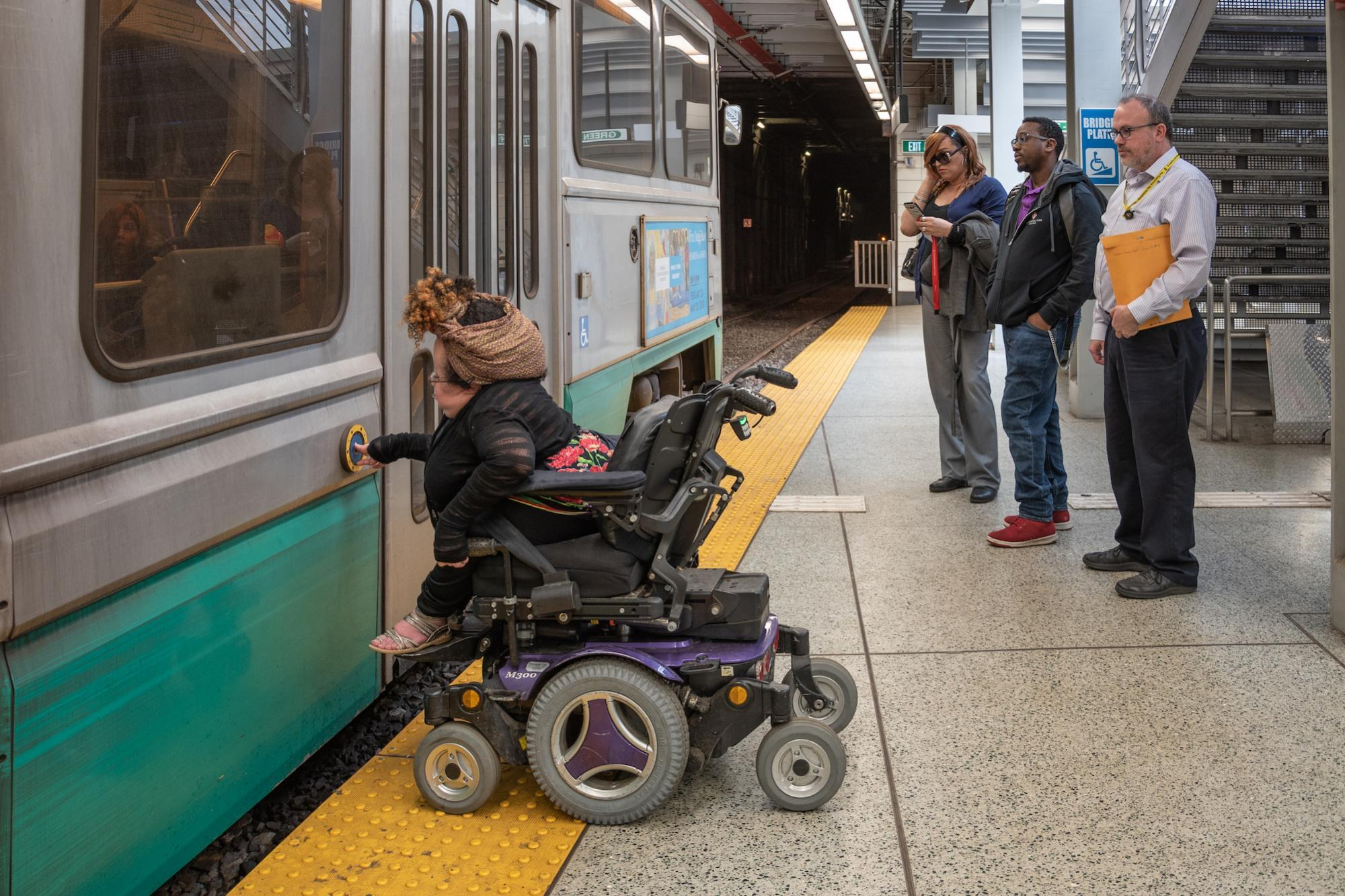 A person in a wheeled mobility device presses the accessibility button on a Green Line train at Government Center Station.