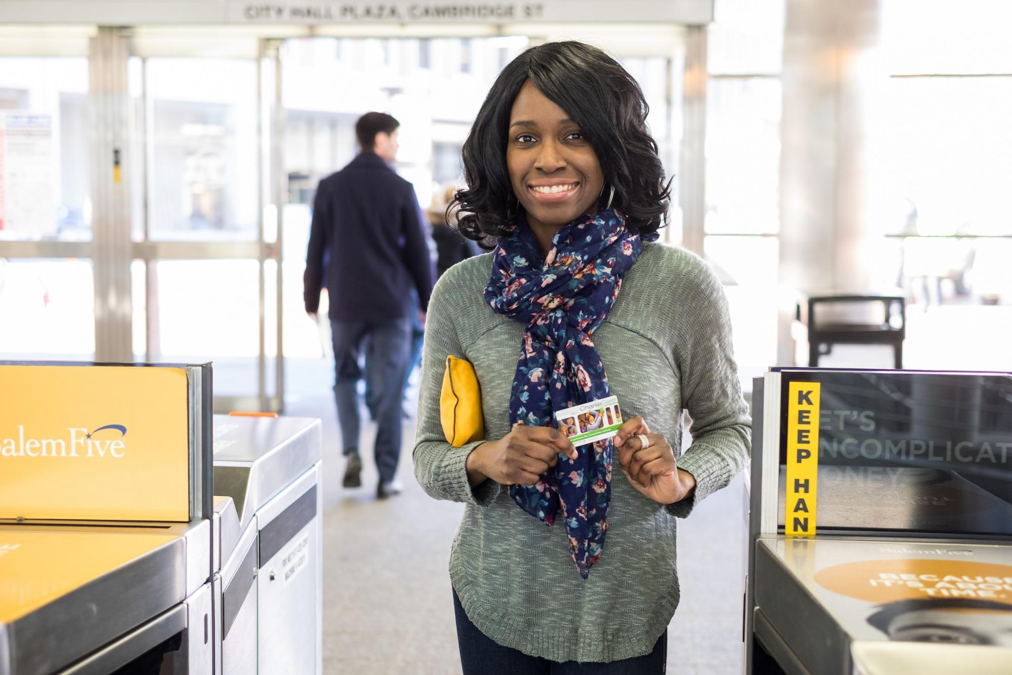 Woman entering fare gate with CharlieCard