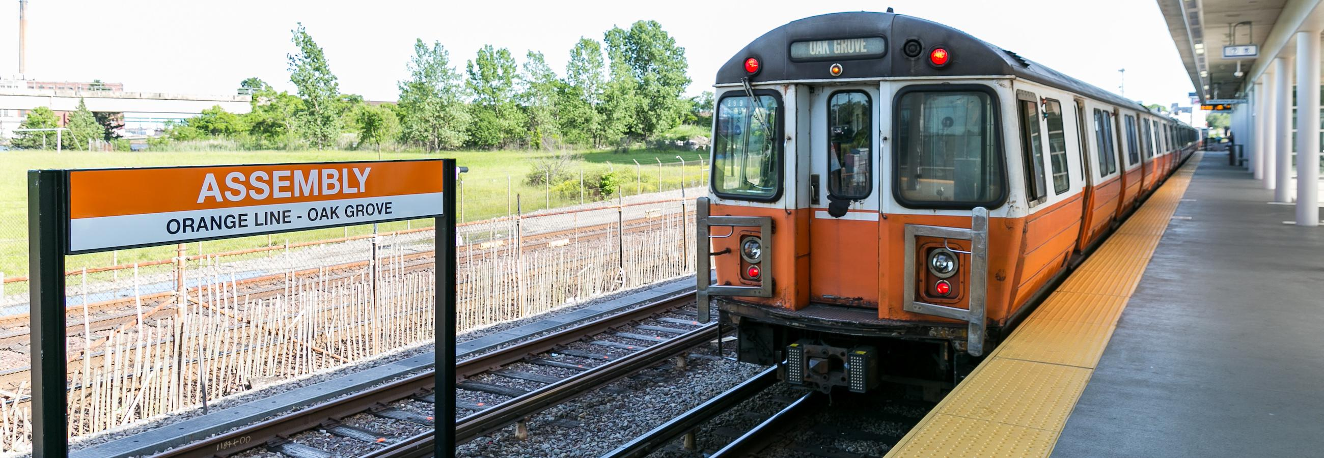 Orange Line Train Pulling into Assembly Station with Sign