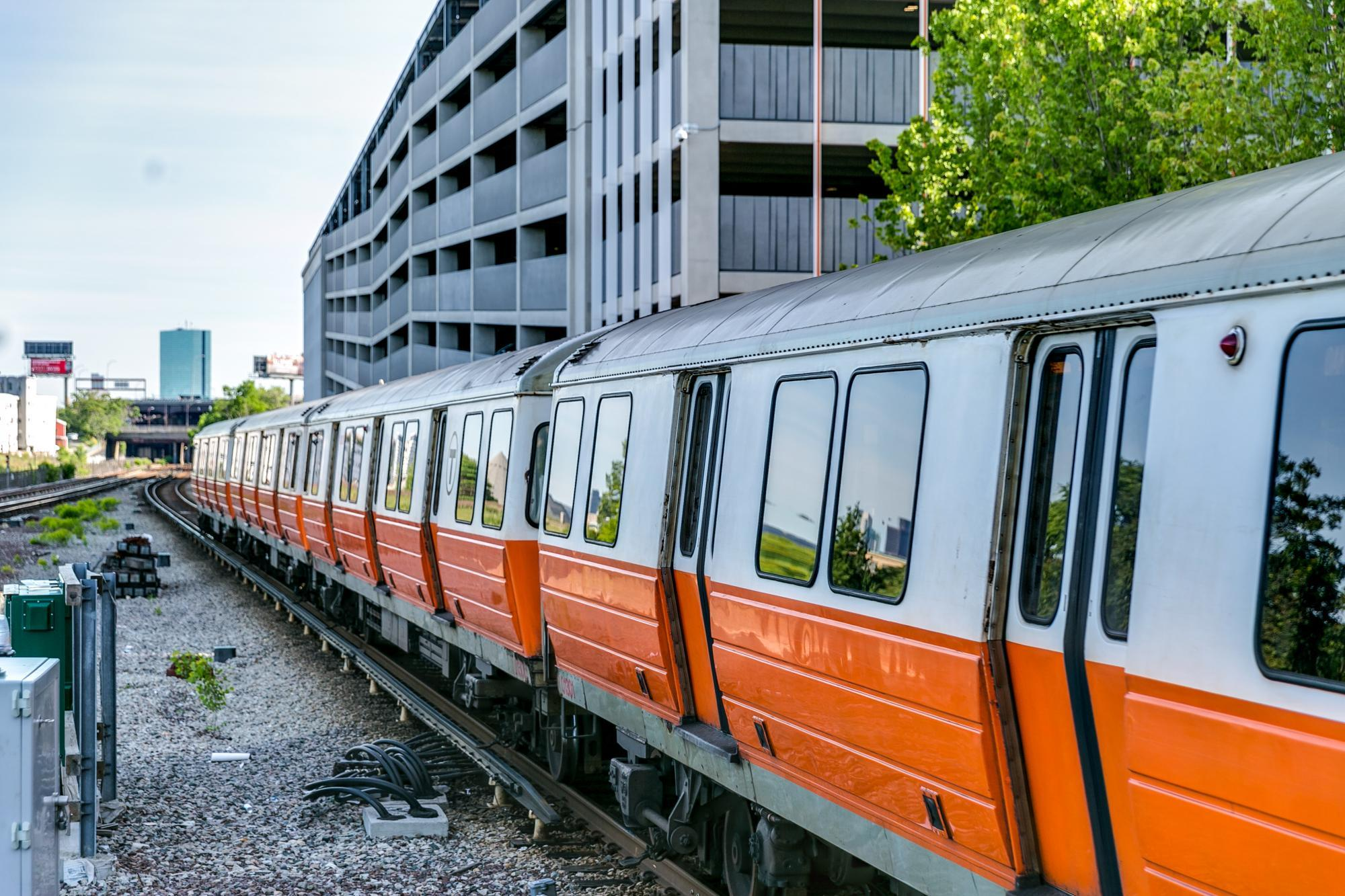 Orange Line train at Assembly Station during the summer, with Boston skyline in background