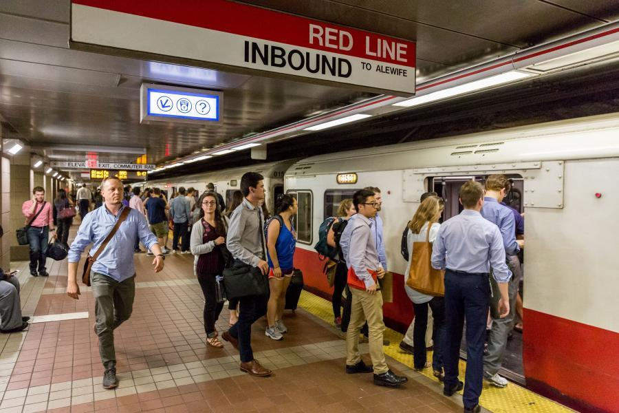 Riders board a Red Line train on the inbound platform of South Station