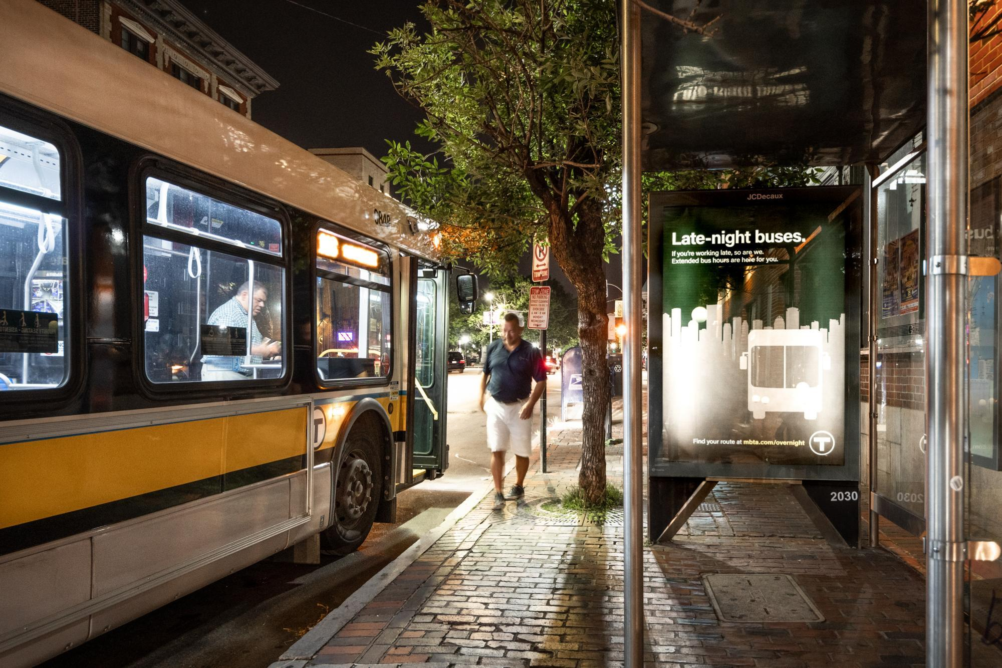"""A bus pulled up to a bus shelter late at night, with a rider walking away, and an ad for late night bus service on the shelter wall, which reads, """"Late-night buses. If you"""
