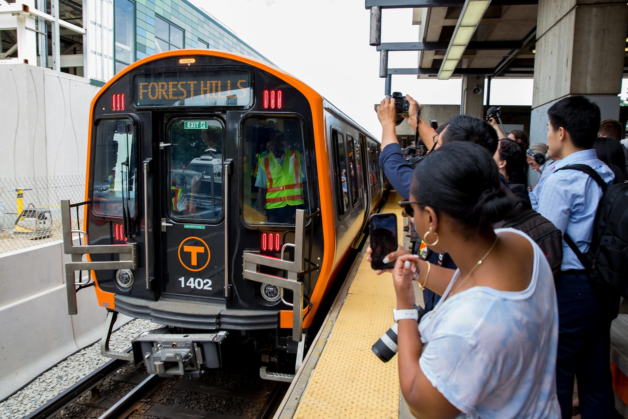 New Orange Line car at Wellington, as a crowd on the platform takes photos.