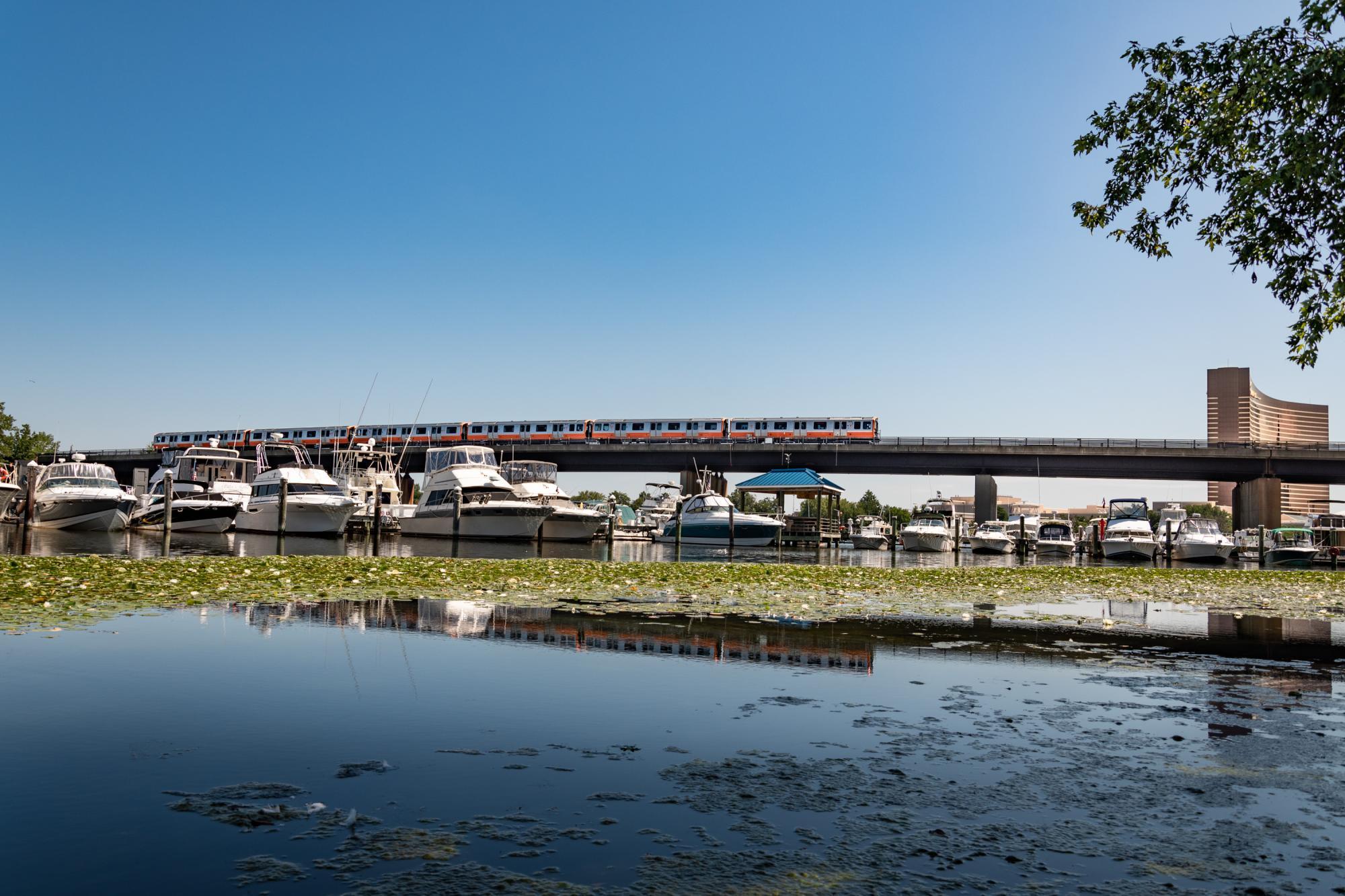 A new Orange Line train travels over the Mystic River, with the Encore casino in the background, boats and water in the foreground, a reflection of the train in the water.