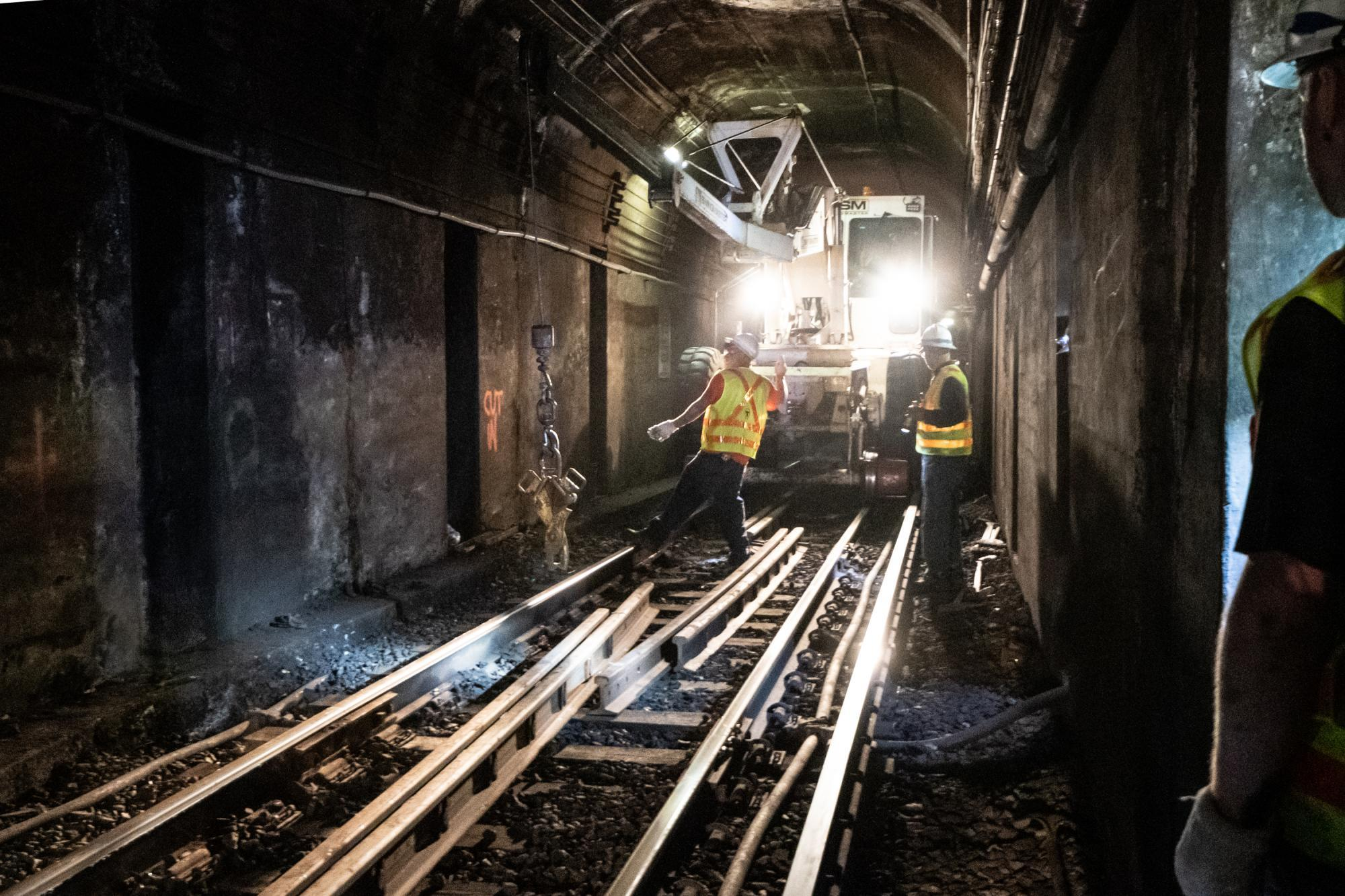 A crew works on rail maintenance in a tunnel, between Bowdoin and Government Center, with heavy machinery in the background.