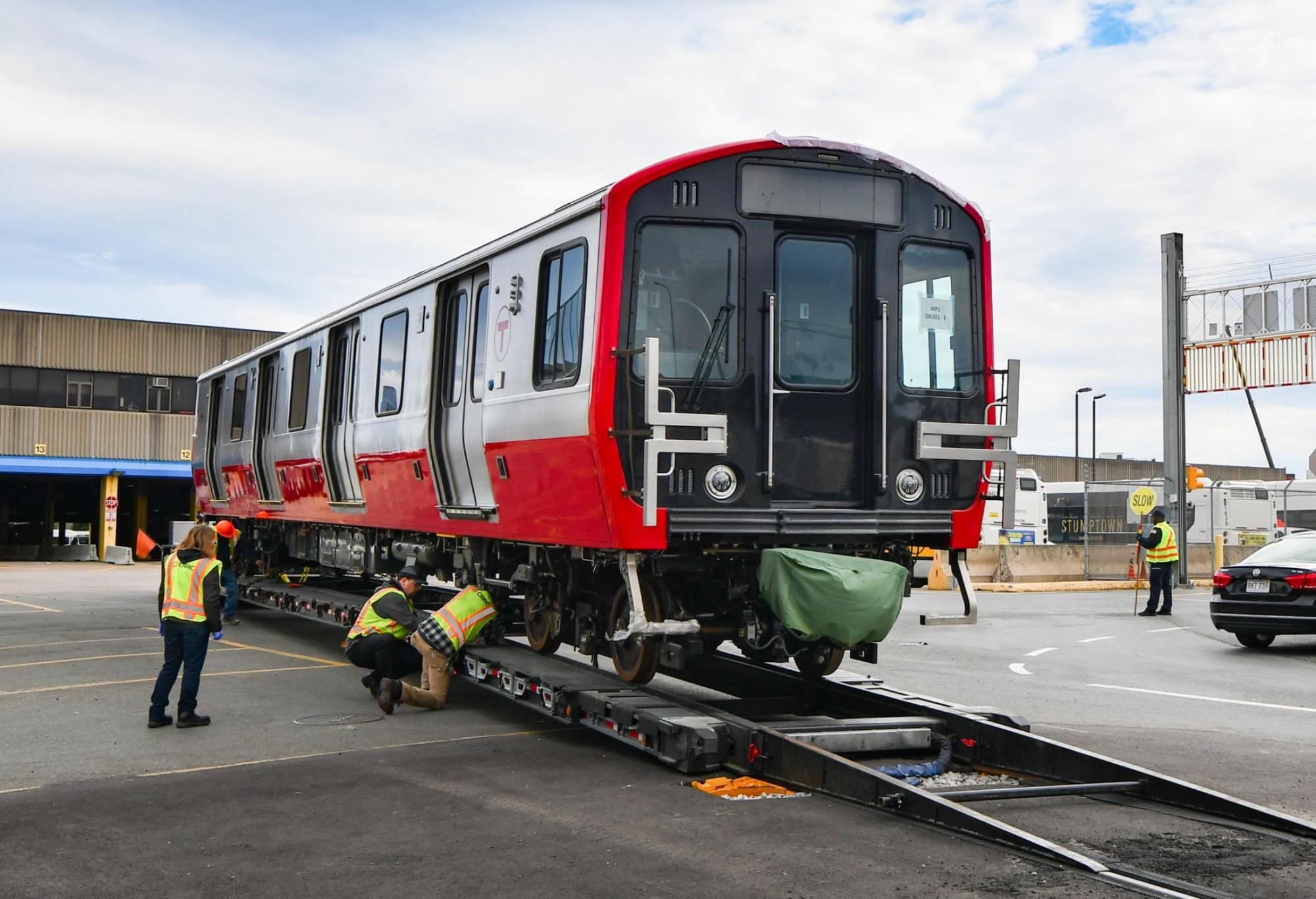 A new Red Line car delievered to Cabot Yard. MBTA workers help get it off the trailer.