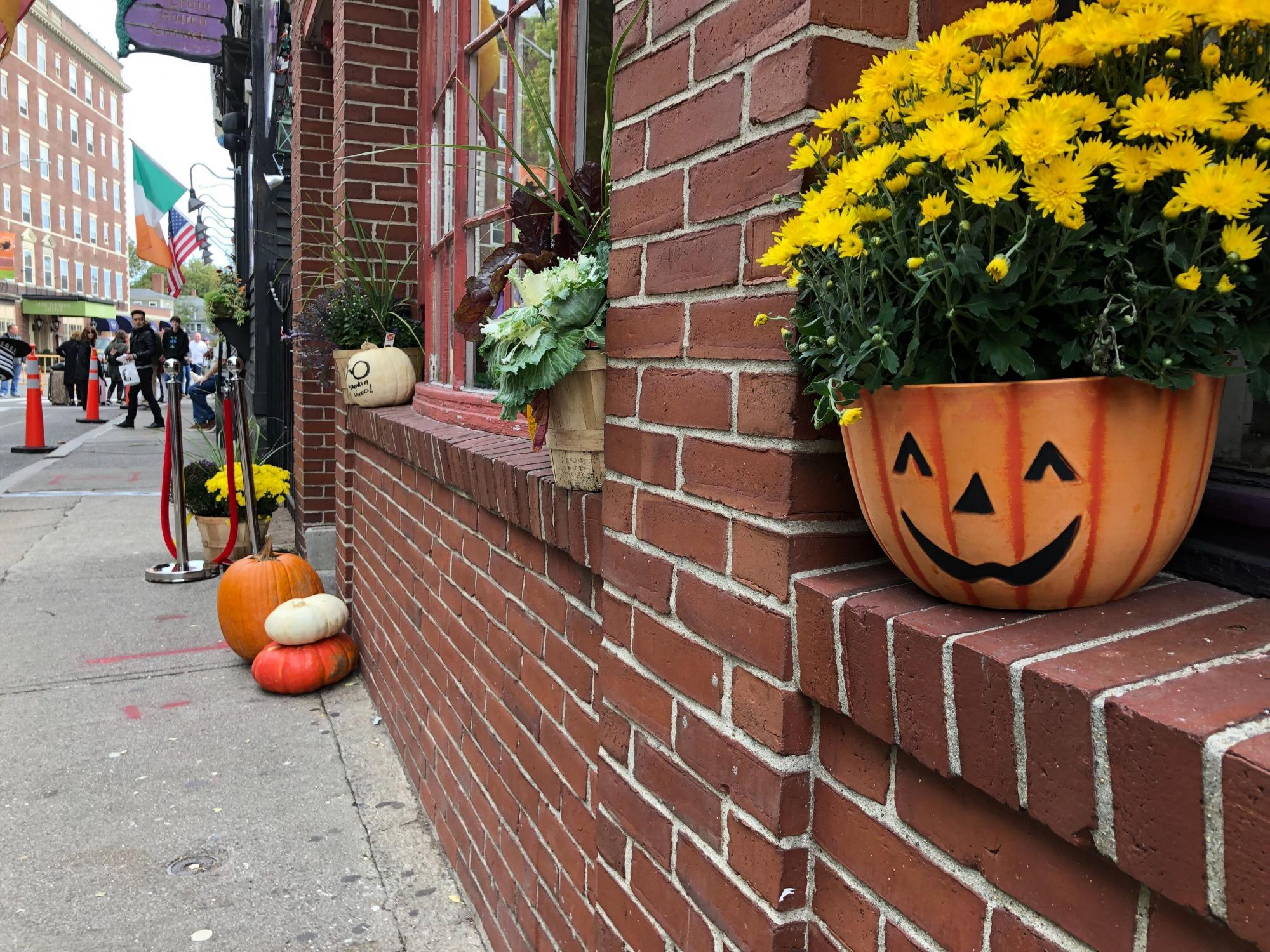 In Salem, a jack-o-lantern planter with flowers sits in a windowsill, with the weekend crowd in the background