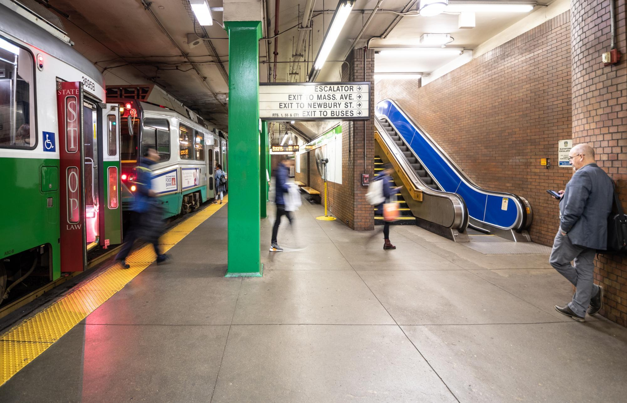 Riders disembark a Green Line train at Hynes Station