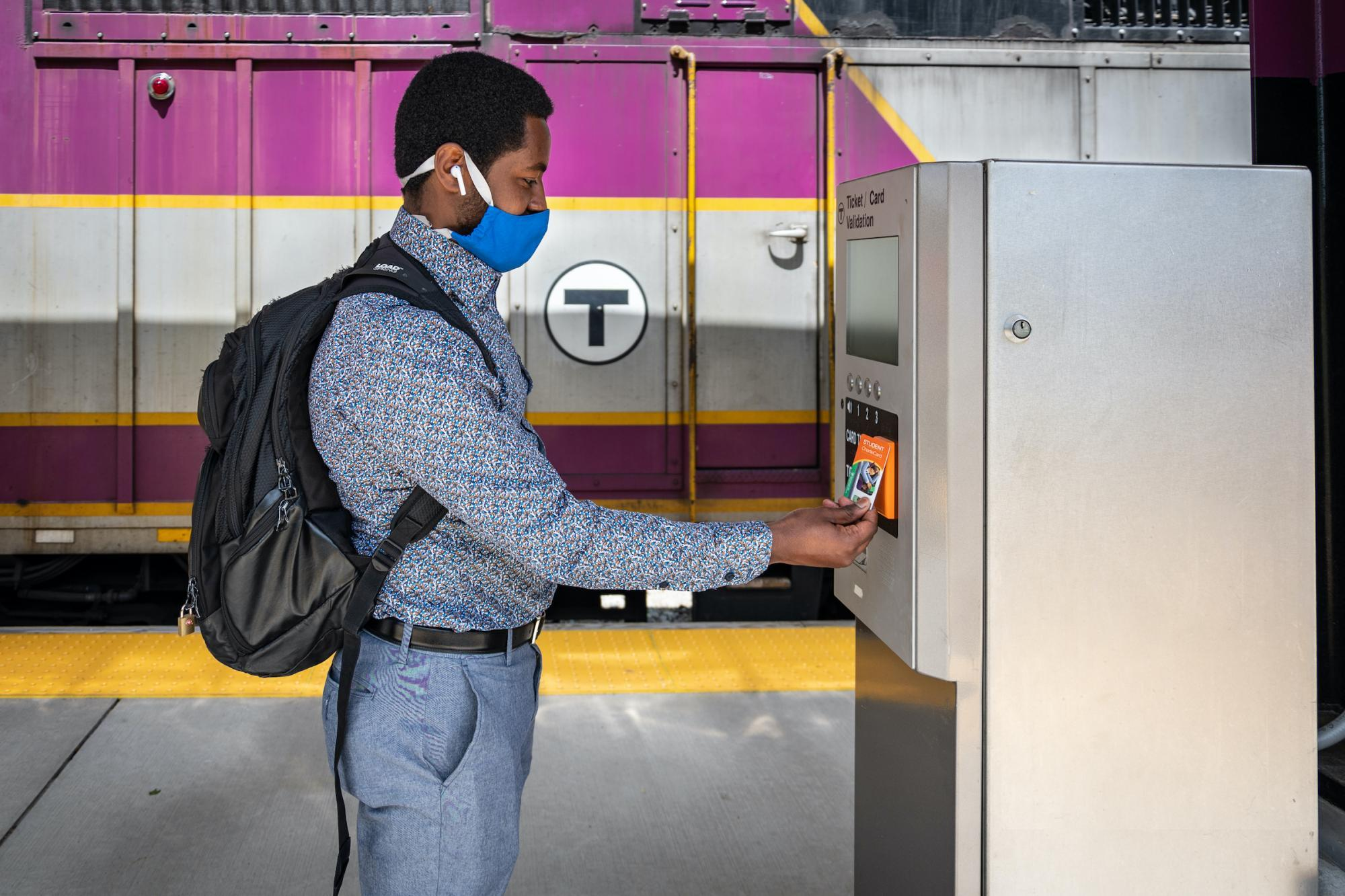 A Commuter Rail rider wearing a face covering uses his CharlieCard at a fare validator at Blue Hill Ave Station.