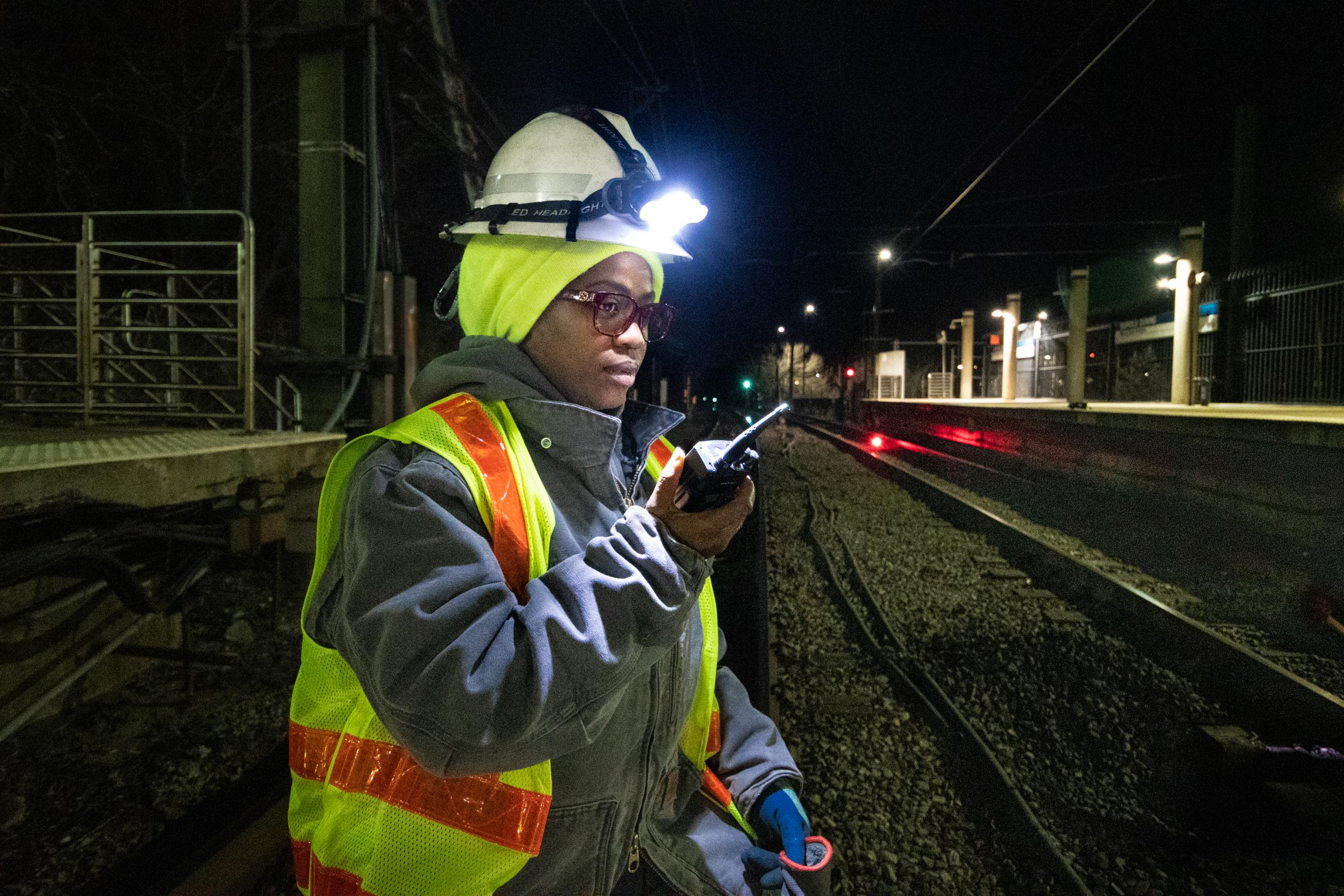 A crew woman at night along the Blue Line tracks, with a headlamp and safety vest