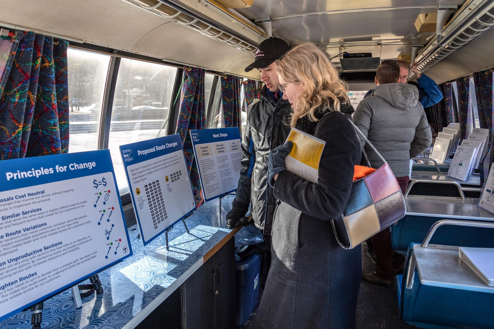 Members of the public browse inside a retrofitted bus with tables featuring informational posters and flyers about the Better Bus Project.