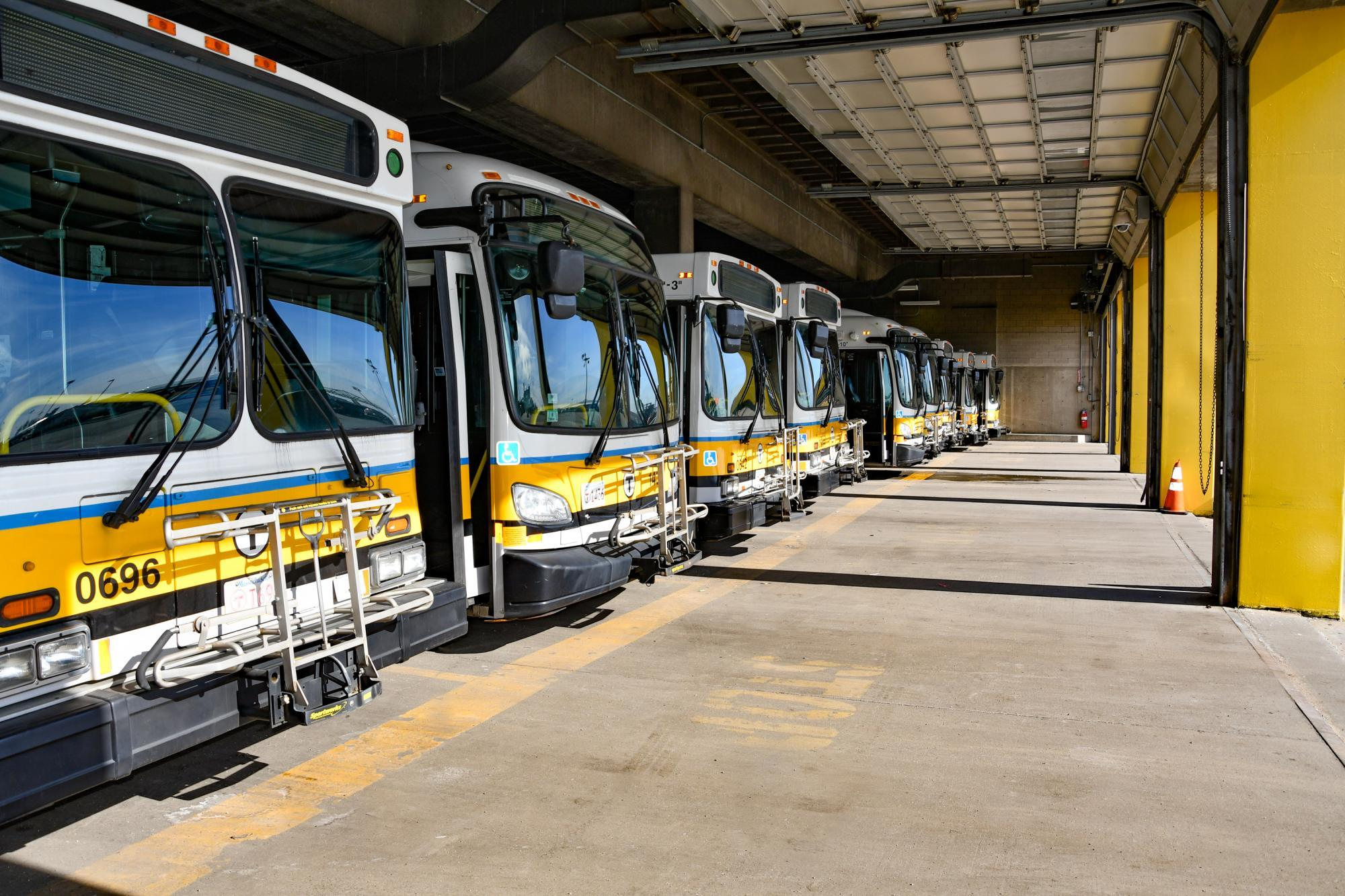 A line of parked buses, with sunlight streaming into the garage
