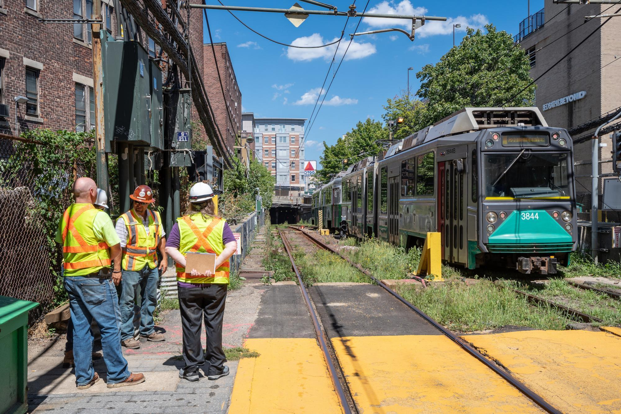 A three-person construction crew stands on the left as a Green Line D train exists the Fenway Portal and pulls into Fenway Station.