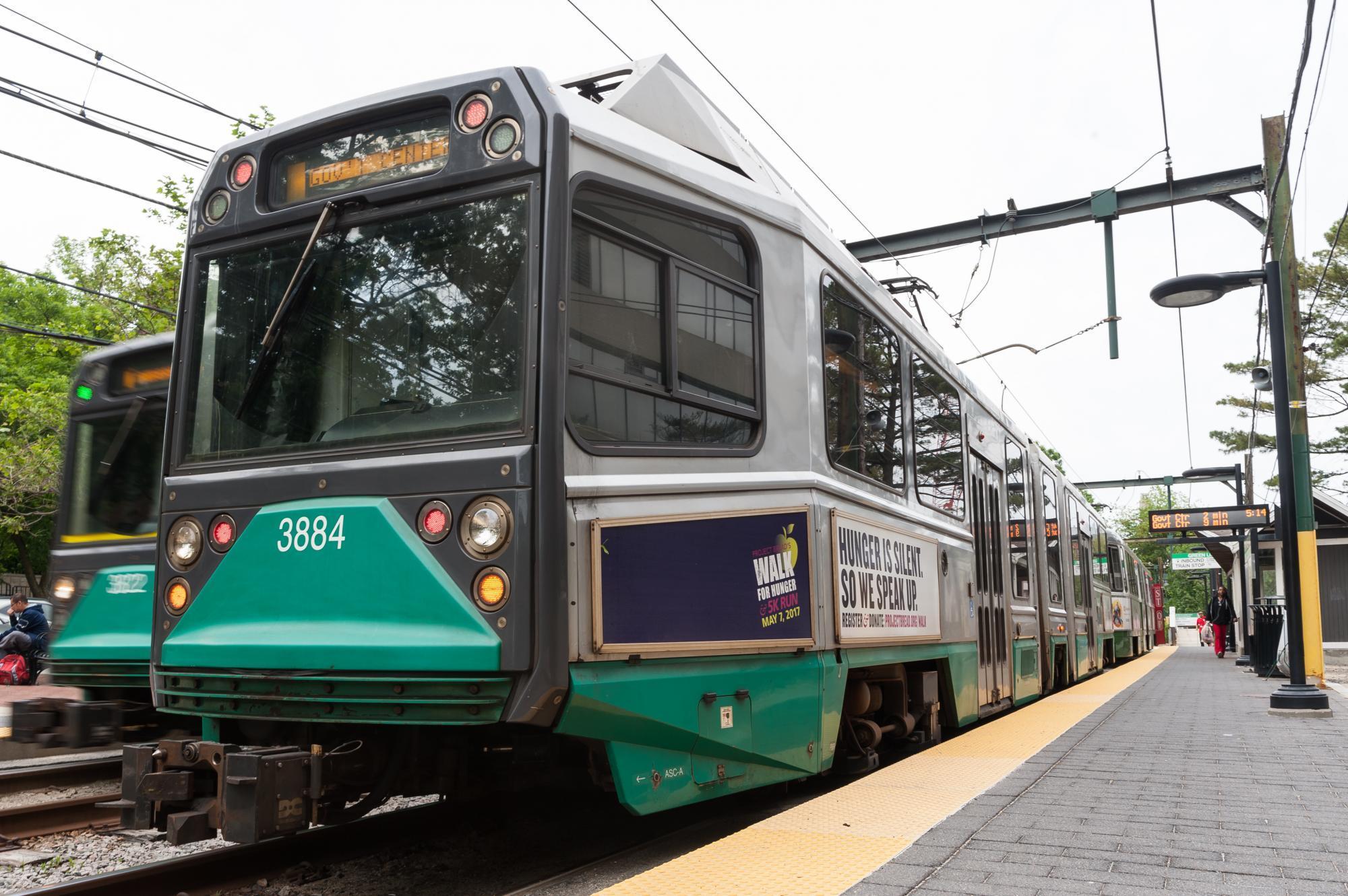 A Green Line train arrives at an above-ground platform.