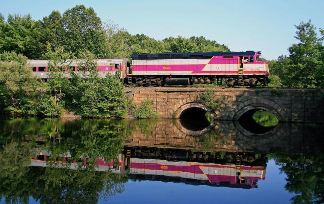 Commuter Rail train crossing a bridge over a river, with lush greenery