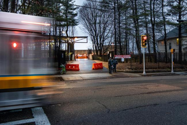 View of Quincy Adams gate from the street, with a bus whirring past, coming from the left