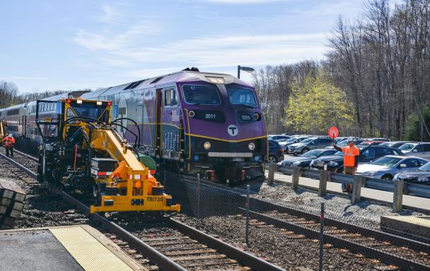 A Commuter Rail train with machinery by its side, the track ties being replaced