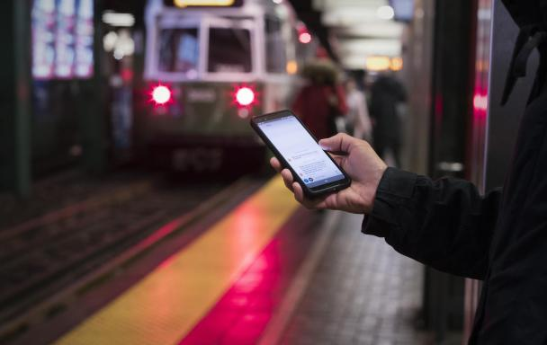 On the Green Line platform at Park Street, a rider holds a smartphone, looking at a T-Alerts text message.