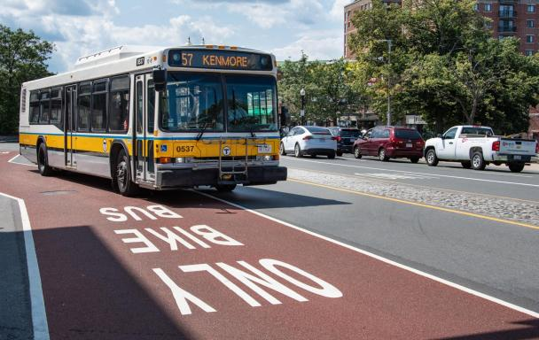 """The 57 bus travels in a dedicated bus lane on Brighton Ave in Allston, with """"Bus Bike Only"""" prominently stenciled in the dark red lane."""