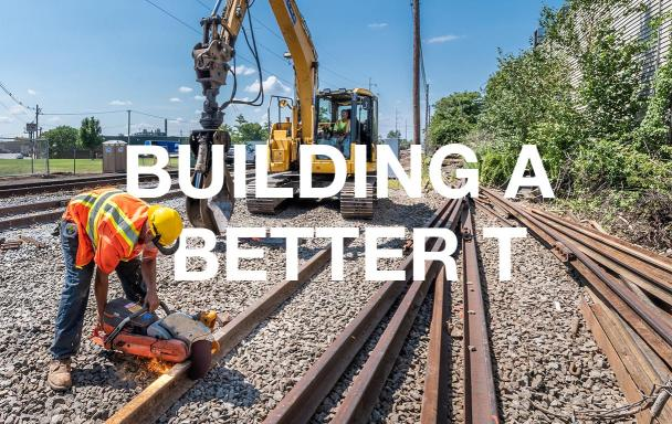 """A crewperson in the foreground cuts rail while another crewperson sits in heavy machinery in the bakground. White text overlaid reads """"Building a Better T."""""""