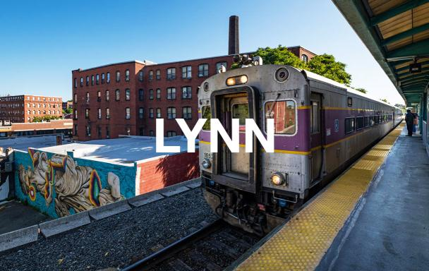 "Overlaid text reads ""Lynn."" A Commuter Rail train pulls into Lynn - Central Square Station, with a mural in the background."